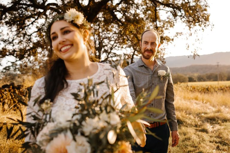 Bride leads groom down a path at Beltane Ranch durning their sunset elopement in Sonoma County