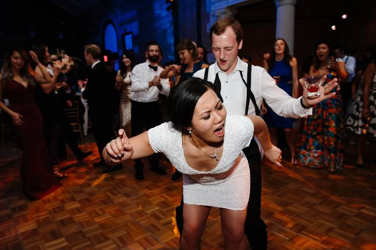Bride and groom singing and dancing in the middle of a circle of friends at their Bronx Zoo wedding