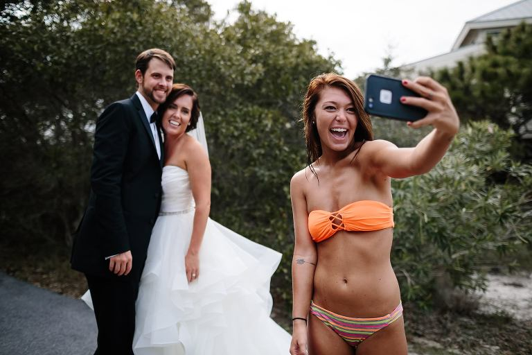 Young woman in bikini taking a selfie with bride and groom during their First Look at their St. George Island wedding