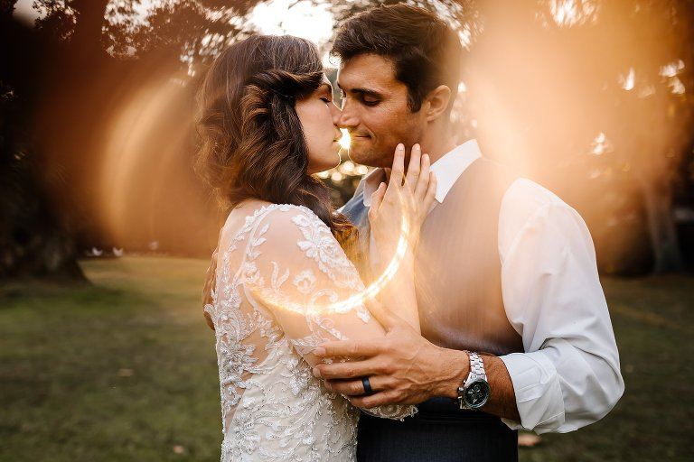 Bride and Groom embracing for a kiss in a circular glowing sun flare at Eden Gardens on 30A