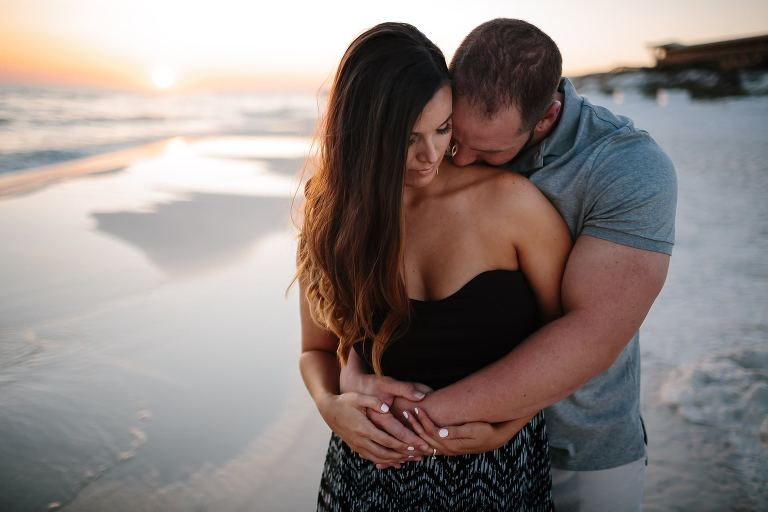 Engagement portrait of muscular fiance kissing his brides neck while on the beach as the sunsets in Santa Rosa Beach Florida