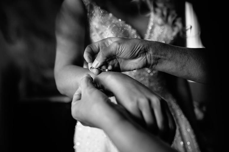 Intimate black and white of the mother of the bride's hands as she clasps a bracelet on the bride