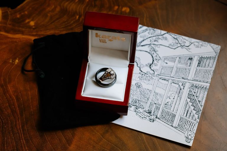 Close up photograph of the weddings bands in the box next to hand drawn illustration of Beltane Ranch