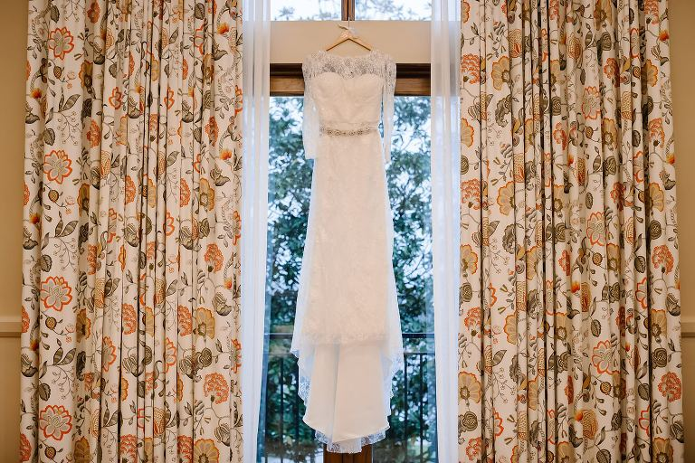 Lace sleeved wedding dress hanging in the bridal suite at Henderson Beach Resort and Spa