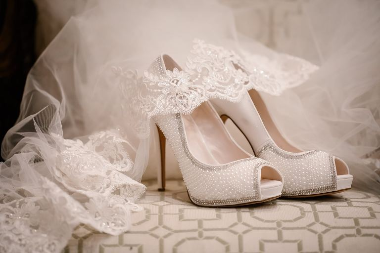 Lace veil and white heels on a chair in the bridal suite