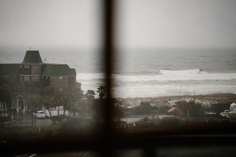 View through the window of the rainy beach from Henderson Beach Resort and Spa