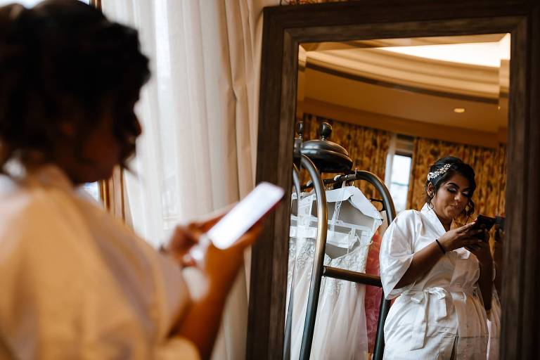 Bride texting while being reflecting in the mirror