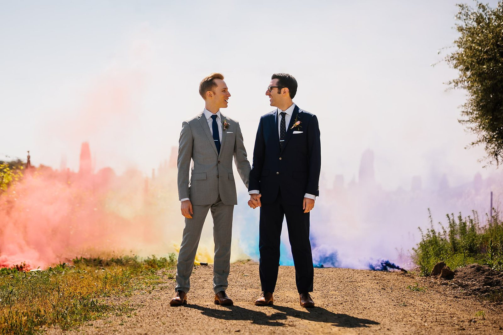Rainbow smoke bombs provide a colorful backdrop in the vineyard where a couple hold hands on their way to their ceremony at Vintners Inn in Santa Rosa