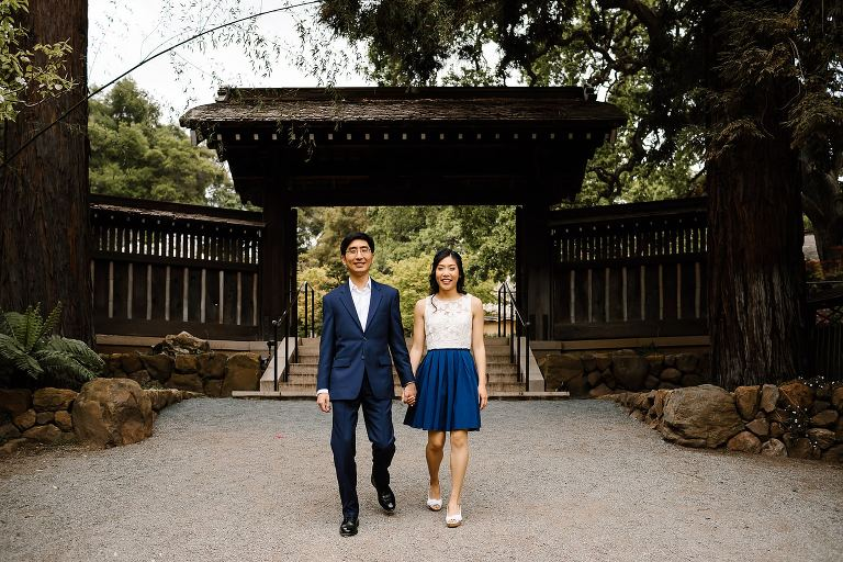 Couple holding hands walking towards camera in front of gates at Hakone Estate and Gardens