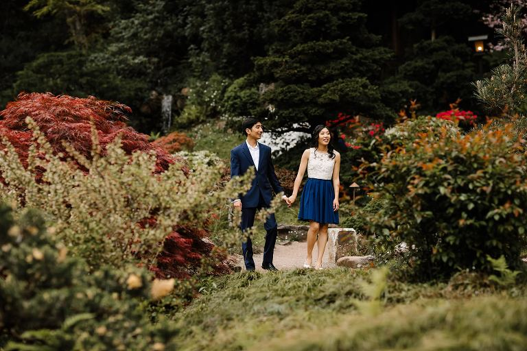 Woman leading man through garden path in Hakone Estate Gardens