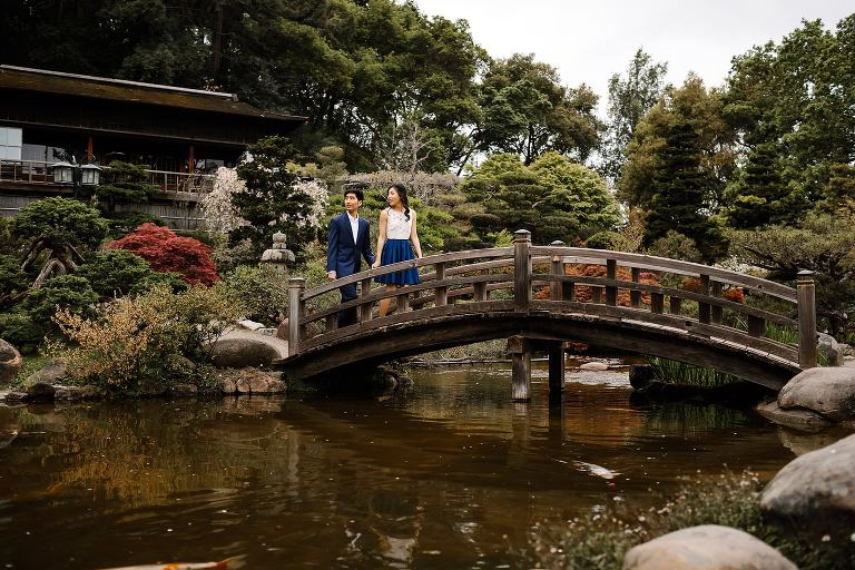 Engaged couple walking over bridge in Hakone Estate gardens