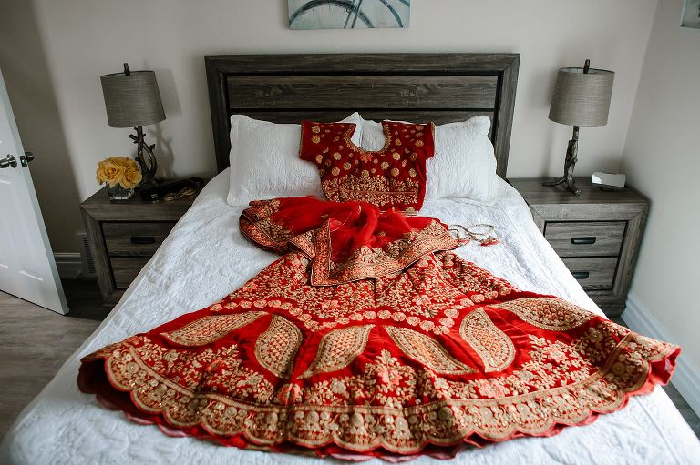 Red and gold Hindu saree on a bed