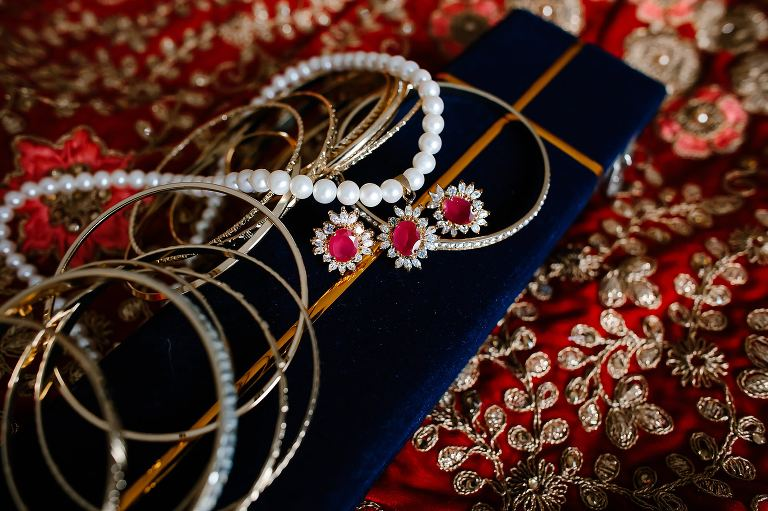 Pearl and ruby necklace with gold bangles lying on hindu saree