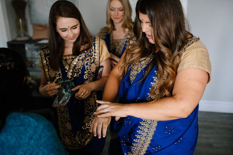 Bridesmaids in royal blue and gold saree's putting on gold bangles