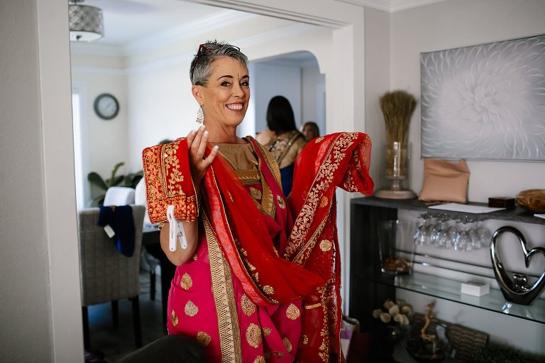Mother of the bride holding red saree