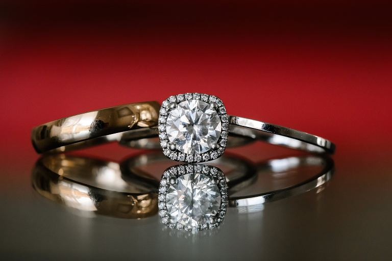 Diamond engagement ring and wedding bands reflected on a table