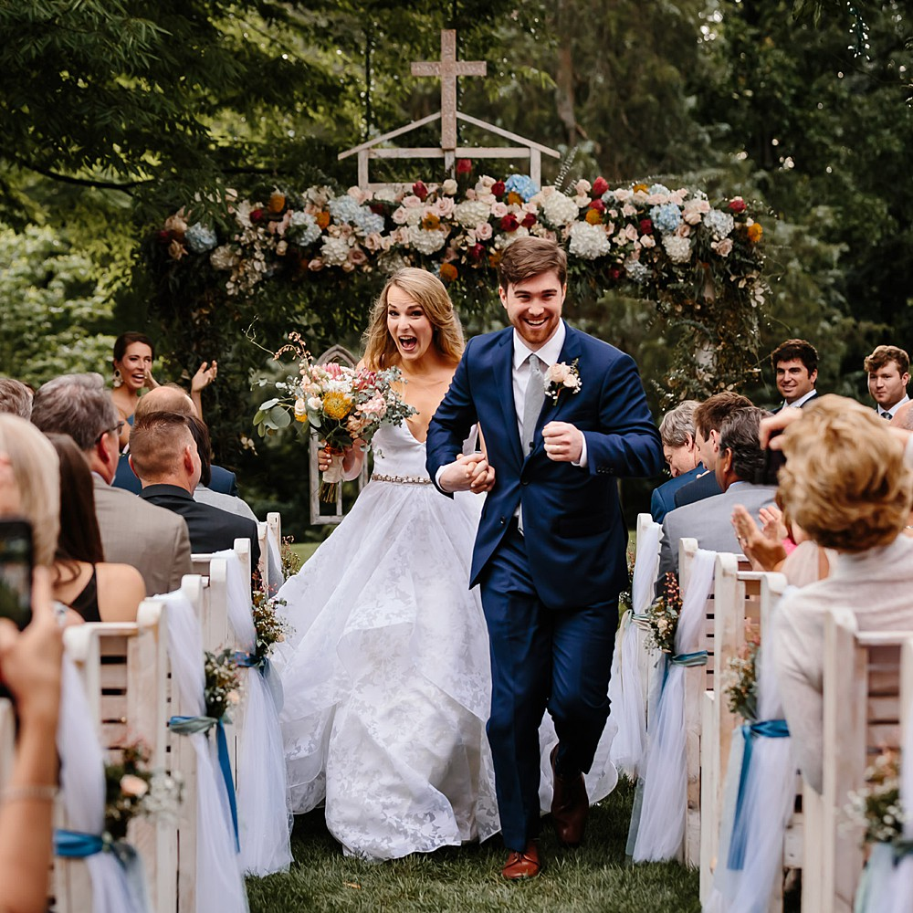 Exuberant couple runs down the aisle at their outdoor wedding at the Graylyn Estate in Winston Salem North Carolina